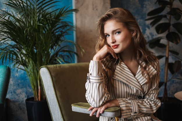 Young attractive lady with wavy hair in striped trench coat playfully