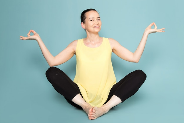 Young attractive lady in yellow shirt and black trousers smiling and posing doing yoga