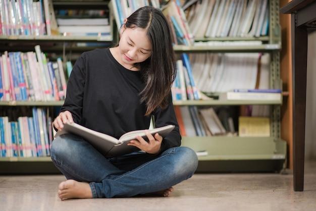 도서관 책 사이의 책을 읽는 젊은 매력적인 사서
