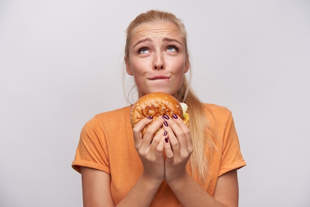 Young attractive long haired blonde woman with ponytail hairstyle wrinkling forehead and biting underlip while looking excusingly upwards with junk food in hands, isolated over white background
