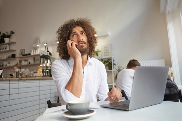 Young attractive long haired businessman having conversation on phone while working out of office with laptop, having cup of coffee in luncheonette
