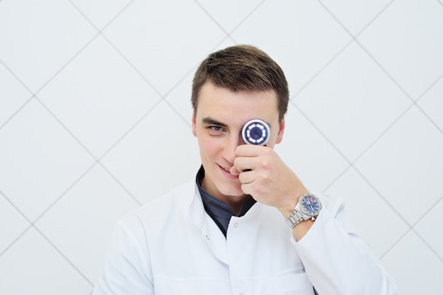 Young attractive male doctor dermatologist with dermatoscope in hand