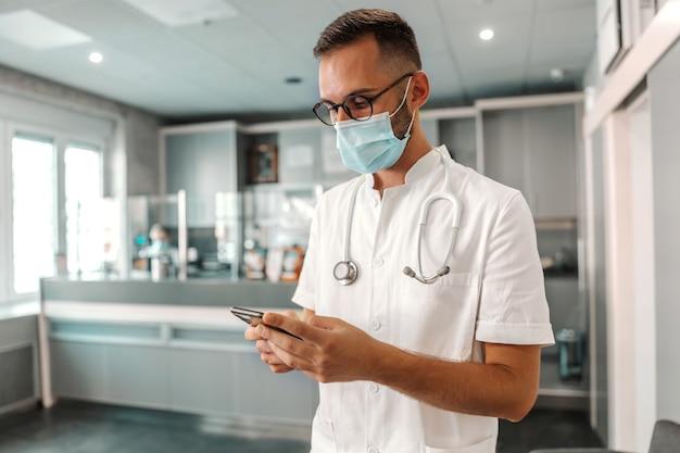 비상을 위해 스마트 폰을 사용하는 얼굴 마스크와 젊은 매력적인 남성 의사