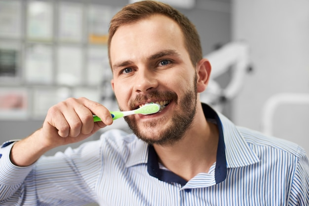Young attractive male is smiling to the camera while cleaning his teeth with a tooth brush in a modern dental office.