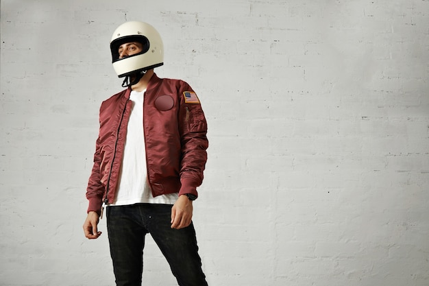 Young attractive male model in black jeans, plain white t-shirt, burgundy nylon bomber jacket and a white motorcycle helmet