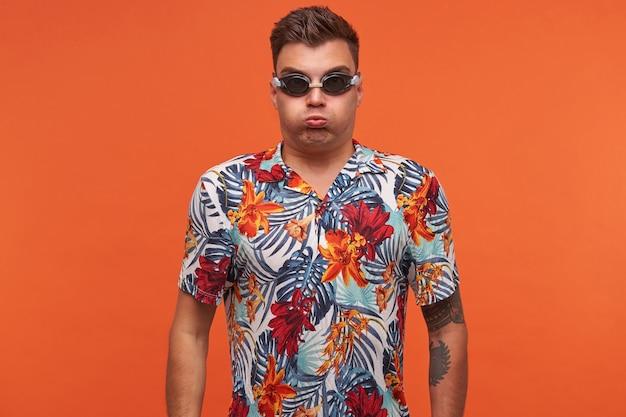手を下に向けて立って、口の中で空気を吸い、息を止め、水泳用メガネをかけている若い魅力的な男性