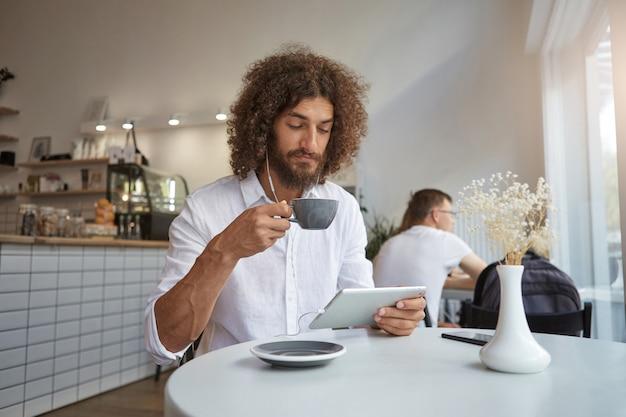 Giovane maschio attraente con barba rigogliosa e capelli ricci castani guardando i video sul suo tablet mentre beve una tazza di tè, in posa sopra l'interno del caffè