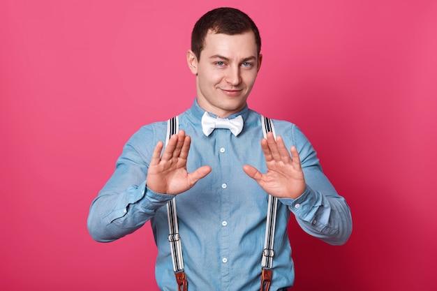 Молодой привлекательный мужчина с короткой прической. модель поднимает ладони и показывает знак остановки, носит синюю рубашку с подтяжками и белую бабочку, изолированную над розовой бетонной стеной.