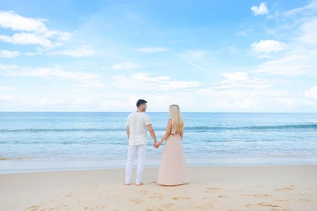 愛の若い魅力的な男性と女性は、白い砂浜と紺碧の海を歩いて抱きしめます。旅行、新婚旅行