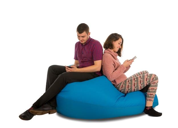 リビングルームや他の部屋の青いお手玉のソファに座って、白で隔離の携帯電話を保持している若い魅力的な男性と女性