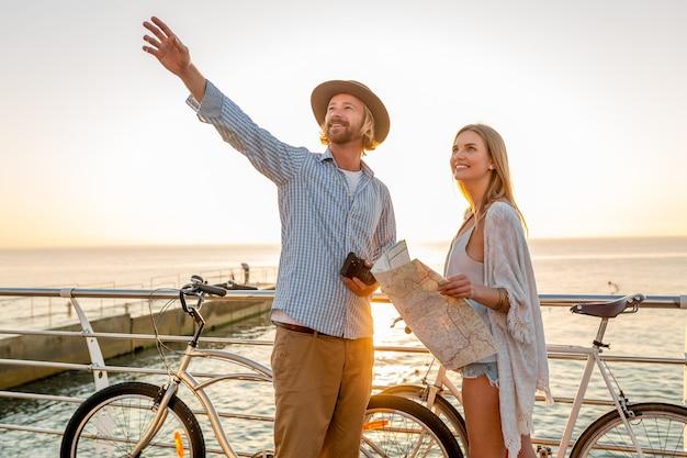 若い魅力的な男と女が自転車で旅行、地図と観光、日没で海沿いの夏休みにロマンチックなカップルを保持している友人が一緒に楽しんで
