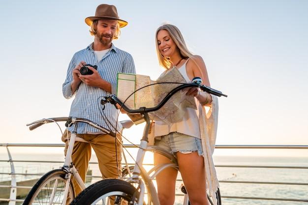 Молодой привлекательный мужчина и женщина, путешествующие на велосипедах, держат карту, наряд в стиле хипстера, друзья веселятся вместе, осматривают достопримечательности, делая фото на камеру