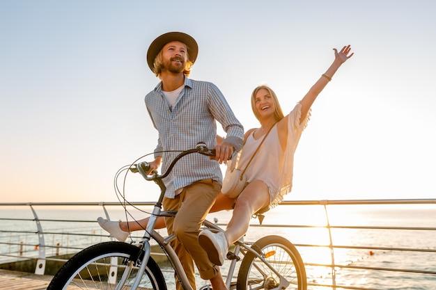 若い魅力的な男と女の自転車、日没で海で夏休みにロマンチックなカップル、自由奔放に生きる流行に敏感なスタイルの服、一緒に楽しんで友達