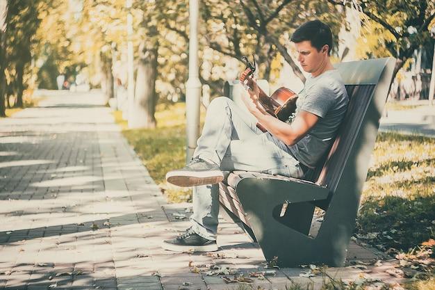 젊은 매력적인 남자는 마지막 화창한 가을 휴가 레트로 렌즈에서 라이브 음악을 즐긴다