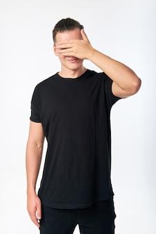 手で目を隠して笑顔の魅力的な若者。