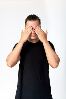 Young attractive man hiding his eyes by hands and smiling