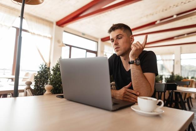 Молодой привлекательный мужчина в стильной черной футболке сидит в кафе и удаленно работает на современном ноутбуке. красивый парень-фрилансер. рабочее время.