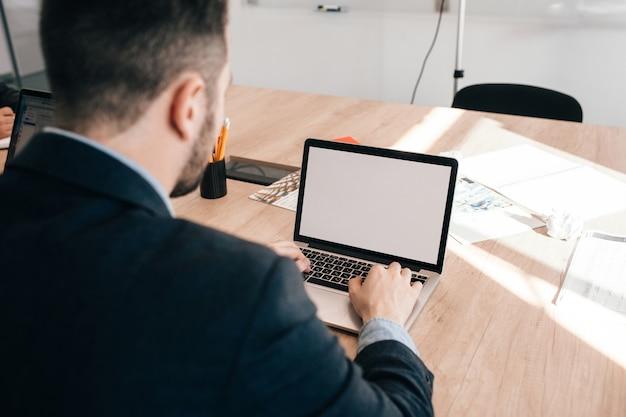 검은 자 켓에 매력적인 젊은이 사무실 테이블에서 일하고있다. 그는 노트북에 입력하고 있습니다. 뒤에서 봅니다.