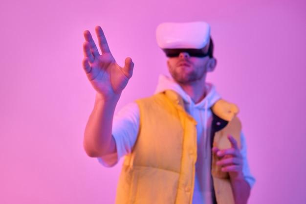 カジュアルな服を着た若い魅力的な男は、仮想現実のメガネを使用して、ネオンピンクで隔離の手で何かに触れようとしています