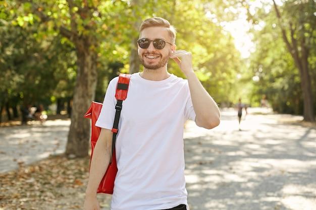 公園を歩いて、カジュアルな服と赤いバックパックを身に着けて、イヤピースを入れて、前向きな感情の概念をサングラスで若い魅力的な男