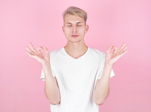 Young attractive man meditates in the lotus position over pink background.