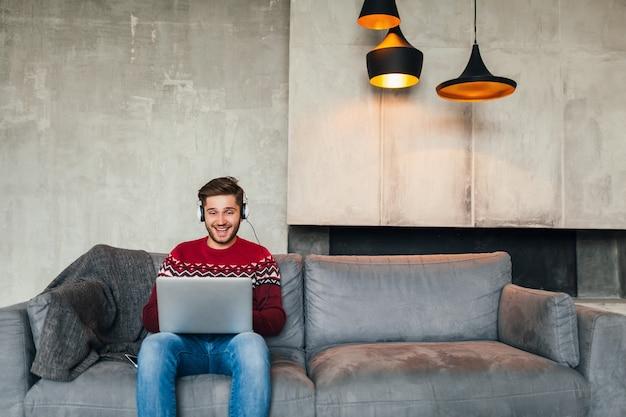 Молодой привлекательный мужчина на диване у себя дома зимой в наушниках, слушает музыку, в красном вязаном свитере, работает на ноутбуке, фрилансер, улыбается, счастливый, позитивный