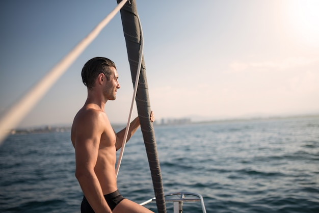 Young attractive man portrait on sailing boat at sunset. real lifestyle image.