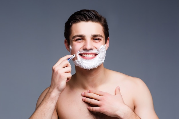 Young, attractive  man shaving .he is passing the razor for the beard while staying on grey wall
