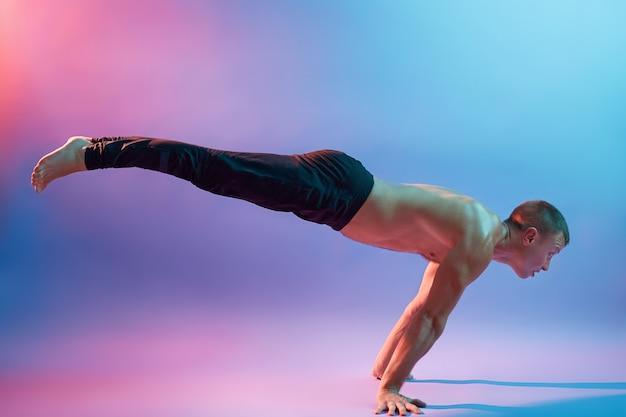 Молодой привлекательный мужчина показывает позы в йоге, стоя на руках, позирует топлес и в черных брюках