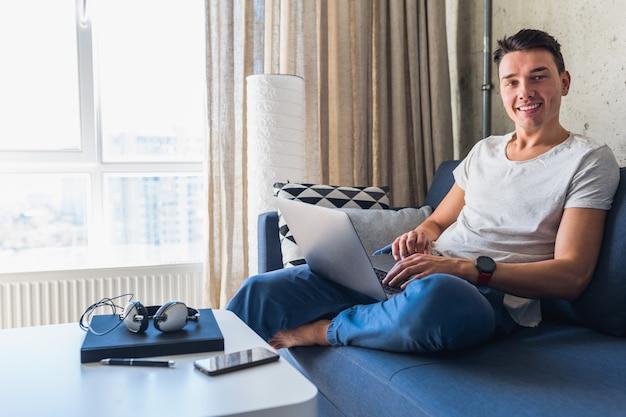 Молодой привлекательный мужчина сидит на диване у себя дома, работает на ноутбуке онлайн, используя интернет