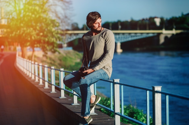 Young attractive man sitting on railing on river bank and looking away