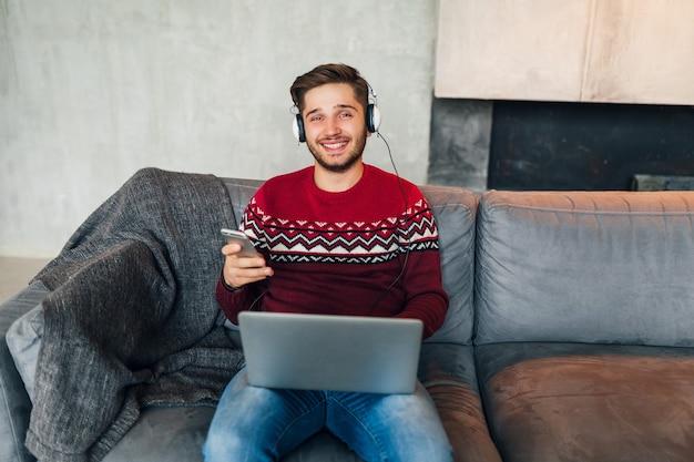 Giovane uomo attraente sul divano a casa in inverno con lo smartphone in cuffia, ascoltando musica, indossando un maglione lavorato a maglia rosso, lavorando sul computer portatile, libero professionista, guardando nella fotocamera