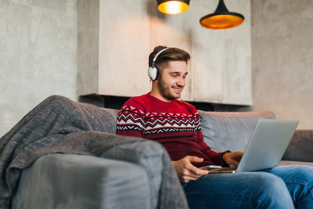 Young attractive man on sofa at home in winter with smartphone in headphones, listening to music, wearing red knitted sweater, working on laptop, freelancer, smiling, happy, positive, typing