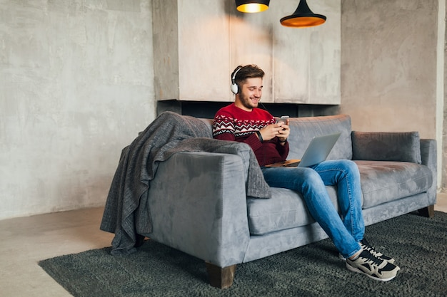 Young attractive man on sofa at home in winter with smartphone in headphones, listening to music, wearing red knitted sweater, working on laptop, freelancer, smiling, happy, positive