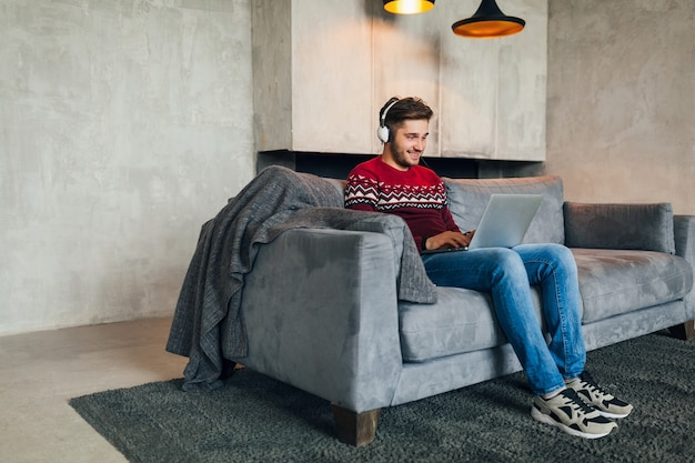 Young attractive man on sofa at home in winter with smartphone in headphones, listening to music, wearing red knitted sweater, working on laptop, freelancer
