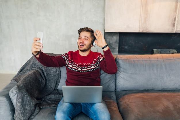 Giovane uomo attraente sul divano a casa in inverno con lo smartphone in cuffia, ascoltando musica, indossando un maglione lavorato a maglia rosso, lavorando sul computer portatile, libero professionista