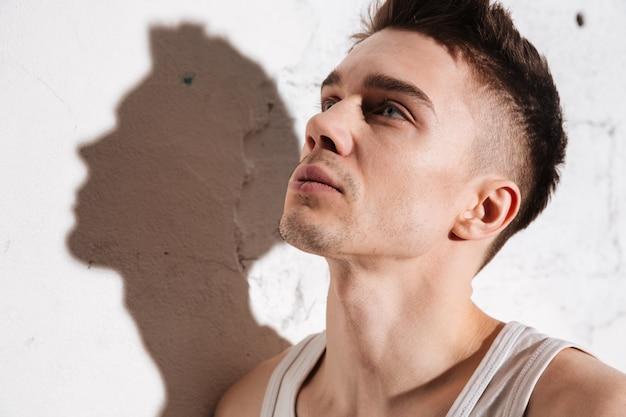 Молодой привлекательный мужчина, стоя на полу позирует