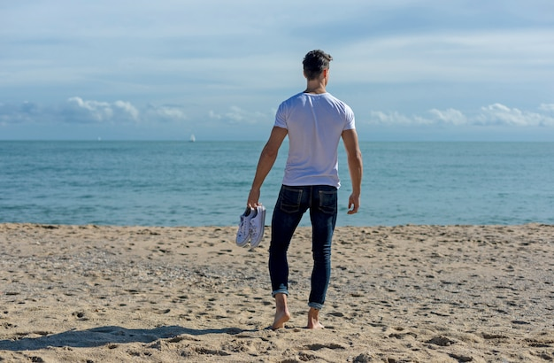 Young attractive man walking on seashore holding a pair of sneakers in a sunny day