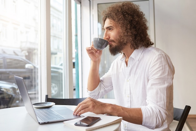 Young attractive man with long curly hair and beard sitting at table in cafe, working out of office with laptop, looking thoughtfully in window while having cup of tea