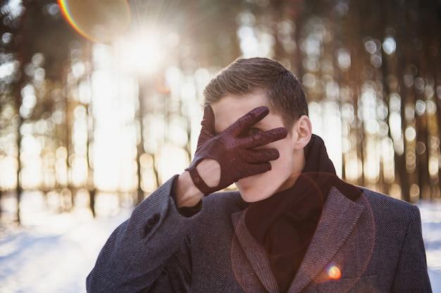 灰色の冬のコートと冬の森を背景にポーズをとって首に黒いスカーフを身に着けている短い髪の魅力的な若者。