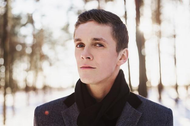 灰色の冬のコートと冬の森に対してポーズをとって首に黒いスカーフを身に着けている短い髪の若い魅力的な男。