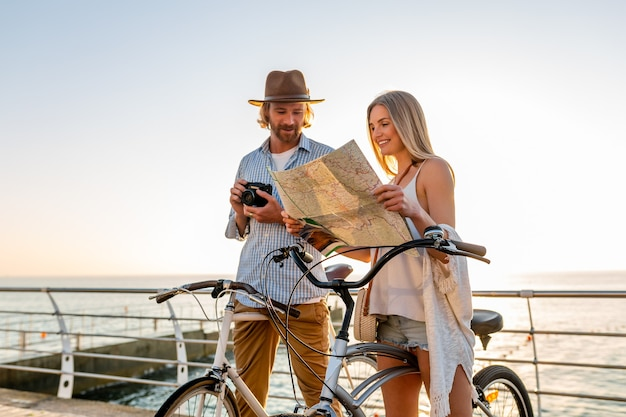Young attractive man and woman traveling on bicycles holding map, hipster style outfit, friends having fun together, sightseeing taking photo on camera, couple on summer vacation on sea at sunset