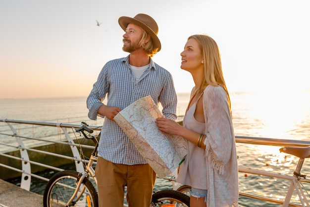 Young attractive man and woman traveling on bicycles, holding map and sightseeing, romantic couple on summer vacation by the sea on sunset, friends having fun together
