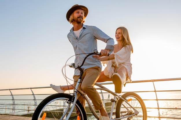 Young attractive man and woman traveling on bicycles, romantic couple on summer vacation by the sea on sunset, boho hipster style outfit, friends having fun together