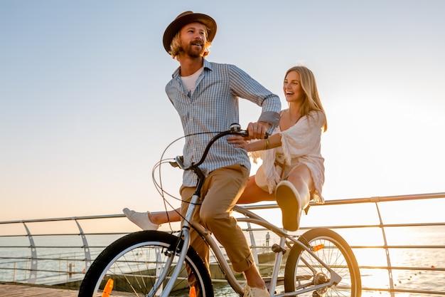 Giovane uomo attraente e donna che viaggiano in bicicletta, coppia romantica in vacanza estiva in riva al mare al tramonto, vestito stile boho hipster, amici che si divertono insieme