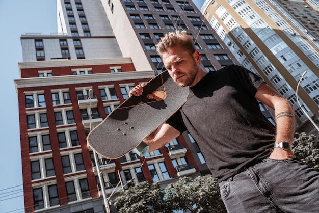 도시 건물 배경에 서 있는 어깨에 나무 롱보드를 들고 있는 젊고 매력적인 남성 금발 남자 스케이트보더는 검은색 스트리트웨어를 입습니다. 잔인해 보인다. 야외 레저 개념입니다.