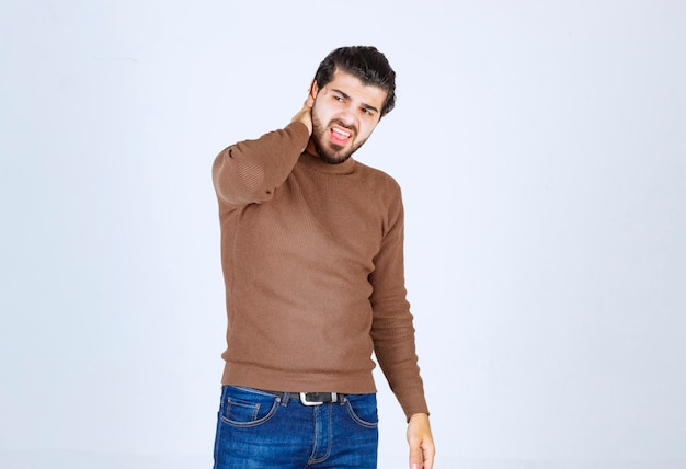 Giovane modello attraente in maglione marrone che fa gesti sul muro bianco.
