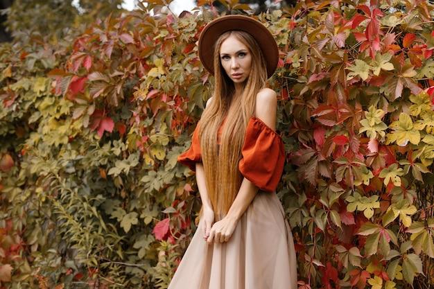 紅葉の近くに化粧をした秋の服の若い魅力的なモデル。閉じる。秋のファッション。ブログ