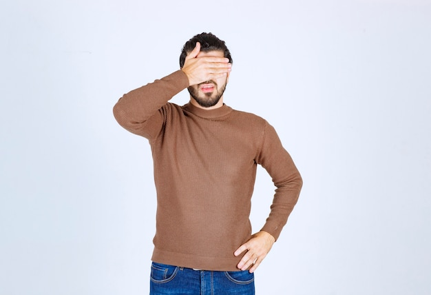 Молодая привлекательная модель в коричневом свитере закрыла лицо над белой стеной.