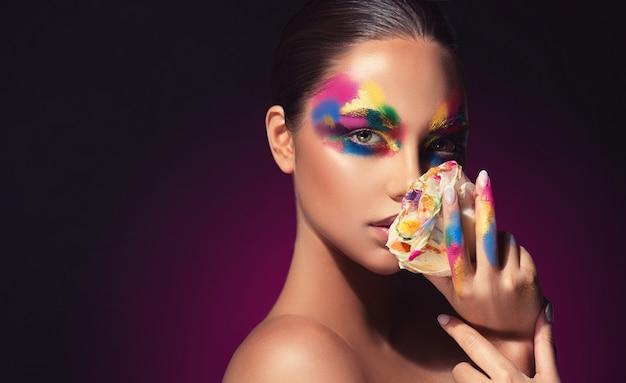顔に色合いのパレットを持つ若い魅力的なモデルは、色の花びらでバラを保持していますメイクアップ